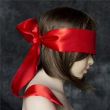 Wide red satin ribbon on the eyes in the form of a mask